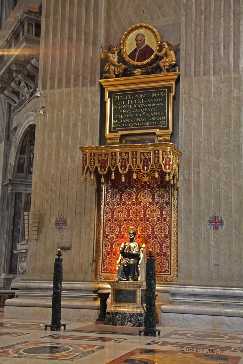 Saint Peters Chair in Saint Peters Basilica surmounted by medalion of Pope Pius IX